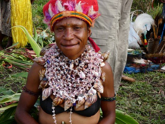Smiling woman with shell necklace and feather headdress at Mount Hagen Sing Sing