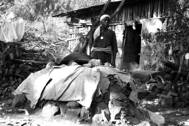 Ethiopian woman cooking in front of home