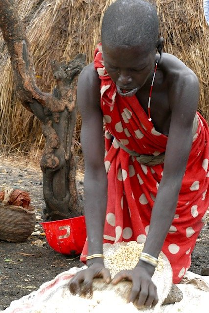 Mursi woman grinding sorghum