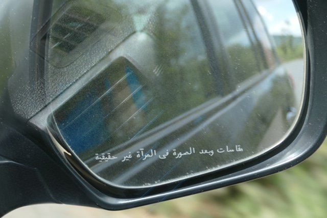 """Objects in the mirror are closer than they appear"" - written in Arabic."