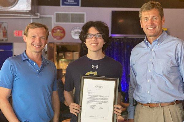 Torras Foundation board members Michael Torras and Daren Pietsch (from left) with scholarship recipient Matthew Pendarvis.